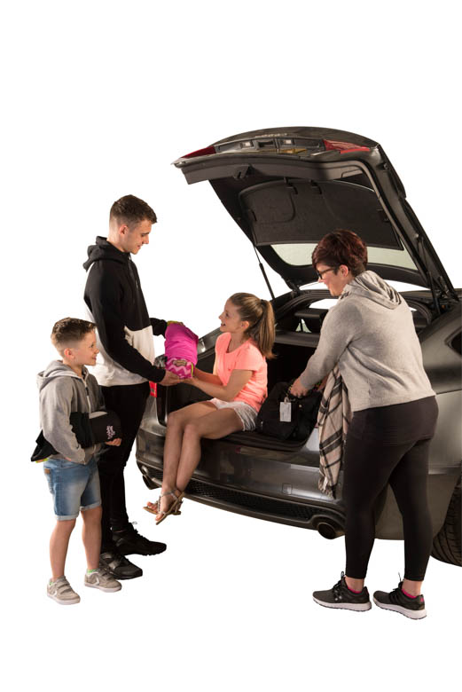Family at boot of car placing seat in girls hands - pink seat 2